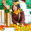 Young woman buying fresh fruits at market — Stock Photo #64267429