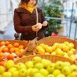 Young woman buying fresh fruits at market — Stock Photo #64267517