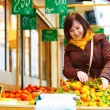 Young woman buying fresh fruits at market — Stock Photo #64267525