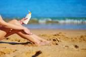 Beautiful woman applying sunscreen on her legs — Stock Photo