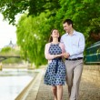 Couple is walking by the water in Paris — Stock Photo #64485785