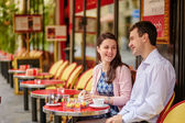 Couple drinking coffee or tea in a Parisian cafe — Stock Photo