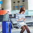 Young passenger at the airport, using her tablet — Stock Photo #66704041