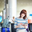 Young passenger at the airport, using her tablet — Stock Photo #66704297