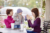 Grandmother, mother and grandson in a cafe — Stock Photo