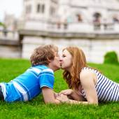 Happy young couple lying on the grass and kissing — Stock Photo