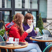 Two cheerful young girls in a Parisian street cafe — Stock Photo