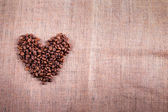 Heart with roasted coffee beans on the burlap background — Stock Photo