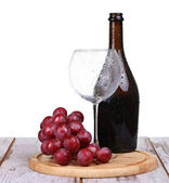 Wine glass with red wine, bottle of wine and grapes isolated over white background — Stock Photo