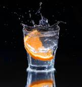 Slice of lemon splashing into a glass of water with a spray of w — Stock Photo