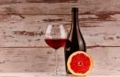 Glas rode wijn, een fles wijn en grapefruit op de Tablet PC — Stockfoto