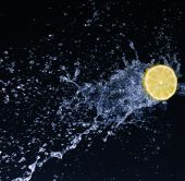 Half a lime falling into the water isolated on a black background — Stock Photo