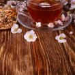 Tea and a branch of cherry blossoms on a wooden — Stock Photo #68451085