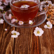 Tea and a branch of cherry blossoms on a wooden — Stock Photo #68455011