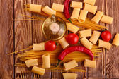 Pasta with cherry tomatoes and other ingredients on wooden table background — Zdjęcie stockowe