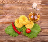 Pasta on the wooden background with tomato, lettuce pepper, olive oil and pepper — Stock Photo
