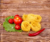 Pasta on the wooden background with tomato, pepper lettuce and pepper — Stock Photo