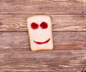 Happy smiley face made of ketchup on a slice of bread — Stock Photo