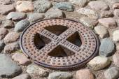 Old steel sewer manhole on the cobblestone road. Text on russian — Stock Photo