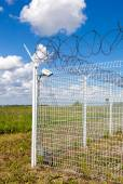 Fence with barbed wire on blue sky background — Stock Photo