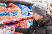 Young woman choosing bath towels at shopping in supermarket stor — Stockfoto