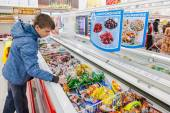 Young boy choosing ice cream at shopping in supermarket — Stock Photo