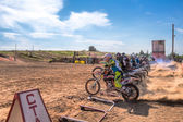 Motocrossers in the starting line waiting for race to start — Stock Photo