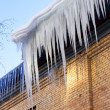 Large icicles hanging on the roof of the house in springtime — Stock Photo #63101555