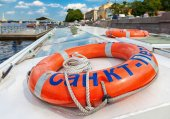 Vibrant orange lifebuoy on the excursion boat in summer day — Stock Photo