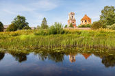 Russian landscape with small tranquil river and old church in th — Stock Photo