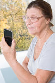 Elderly woman looking at the screen of mobile phone and smiling. — Stock Photo