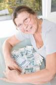 An elderly woman with a bunch of Russian money and savings book. — Stock Photo