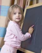 "Girl two years wrote in chalk on the blackboard the number ""one"" — Stock Photo"