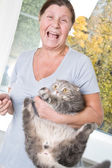 An elderly woman trying to keep the cat — Stockfoto