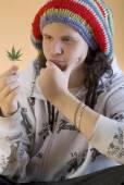 Young rapper ponders marijuana leaf — Stock Photo