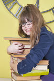 Girl in glasses hugging a stack of books — Stock Photo