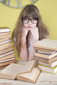 Girl in glasses sitting behind books — Stock Photo