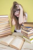 Girl sitting with lots of books and grabs his head — Stock Photo