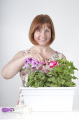 Middle-aged woman taking care of flowers — Стоковое фото