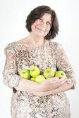 Elderly woman holding a green apple — Stock Photo