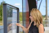Woman looking a timetable in a station — Stock Photo