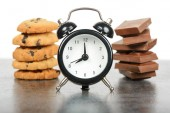 Black alarm clock and sweets — Stock Photo