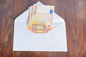 Open envelope with euro banknotes on table — Stock Photo