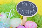 Closeup ester eggs in nest with chalkboard — Stock Photo