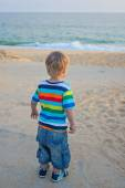 Little boy standing on the beach on sunset — Stock Photo