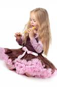 Girl in tutu skirt playing with party blower — Stock Photo