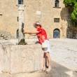 A tourist in the old town at the source of water. Rhodes. Greece — Stock Photo #62550707