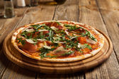 "Italian pizza ""Parma"" on a wooden table. — Stock Photo"