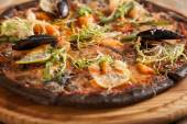 "Italian pizza ""Di Mare"" with black dough and seafood on wooden t — Stock Photo"