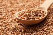 Wooden spoon on scattered buckwheat. — Stock Photo